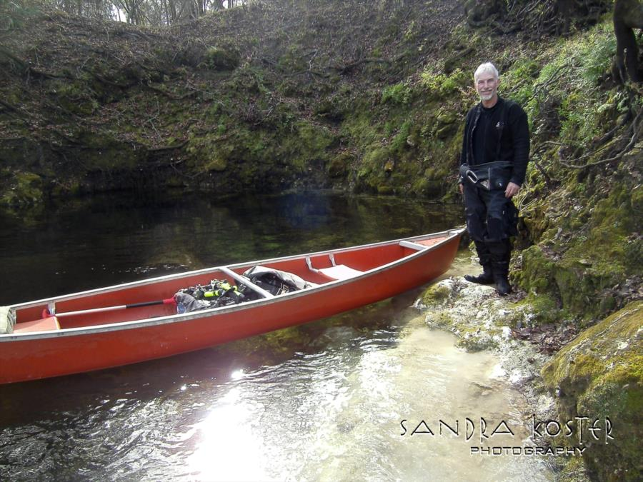 Lineater Spring - Guy Bryant by the canoe with cave entry to his right