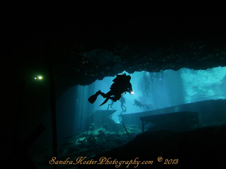 Blue Grotto Dive Resort - Divers with lights entering the cavern zone