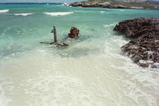 Water Cay - Small beach and remains of Cuban fishing skiff