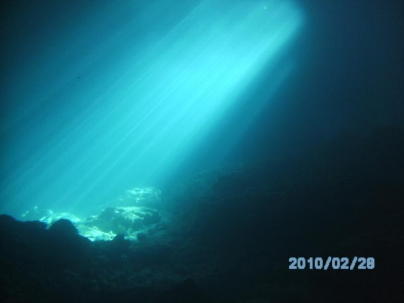 Shafts of light underwater from the hole in the roof of the grotto