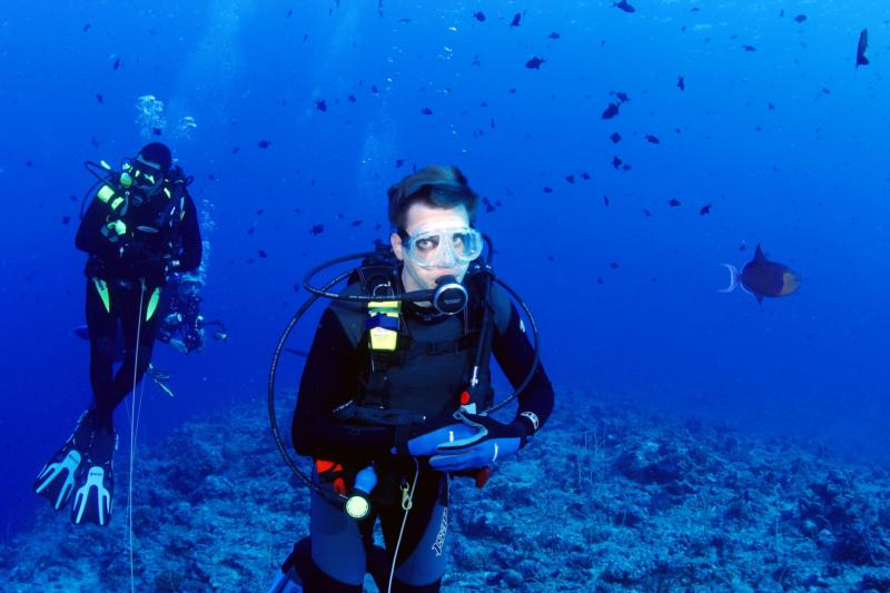 Me in the backround on a reef hook, Blue Corner Palau